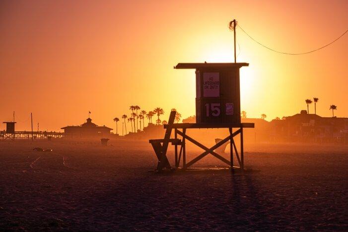 Ein wunderschöner, stimmiger Sonnenuntergang am Newport Beach Pier mit Palmen und Rettungsschwimmerhäuschen